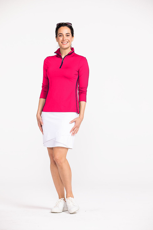 Woman golfer wearing a raspberry red Keep It Covered longsleeve golf top and a white Wrap It Up golf skort