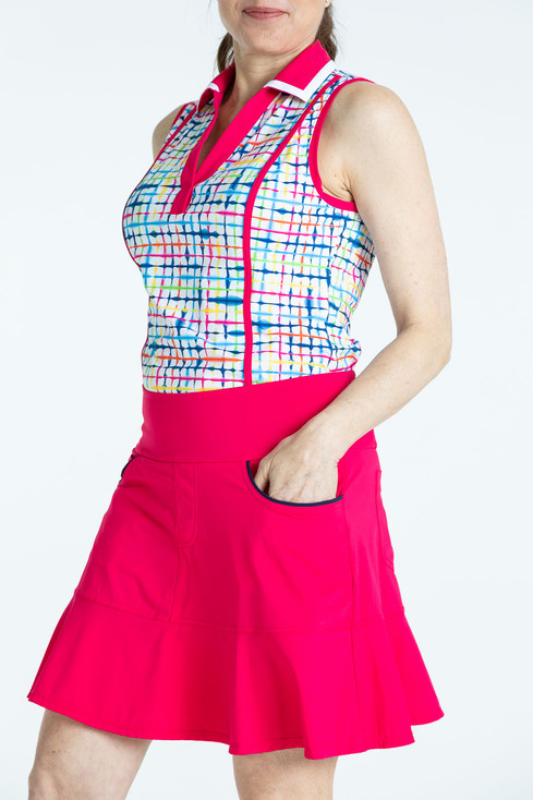 Woman golfer wearing a raspberry red Fit and Flare golf skort and a blurred lines Shape Shifter sleeveless golf top