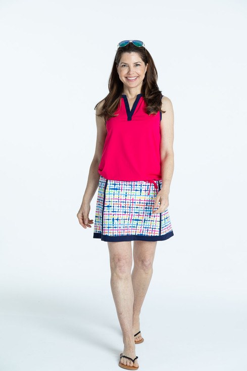 Smiling woman wearing a blurred lines Fresh and Flirty golf skort with a raspberry red Free and Easy sleeveless golf shirt