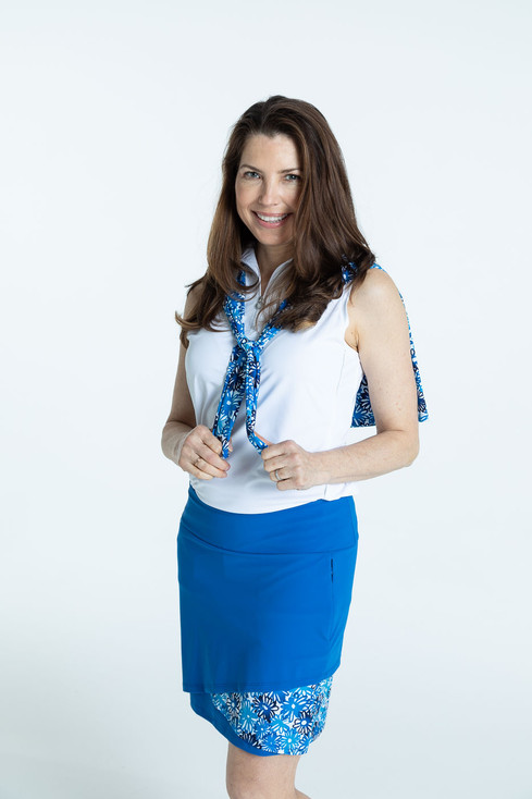 Smiling woman wearing a blueberry blue Wrap it Up golf skort and a white/white Keep if Covered sleeveless golf top