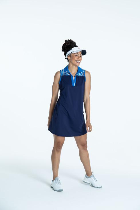 Woman wearing a navy blue Chip Shot sleeveless golf dress and a white No Hat Hair Visor