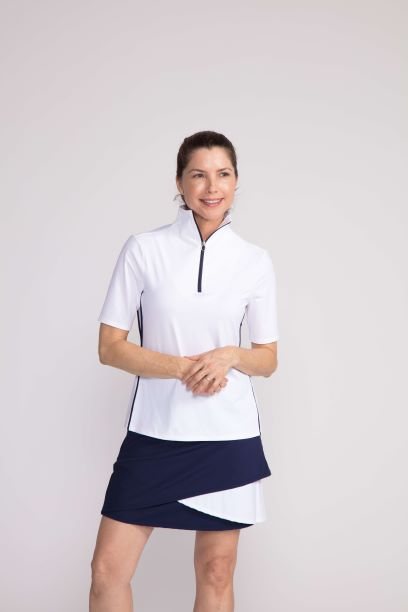Woman wearing a white Keep It Covered shortsleeve top and a black and white Wrap It Up golf skort
