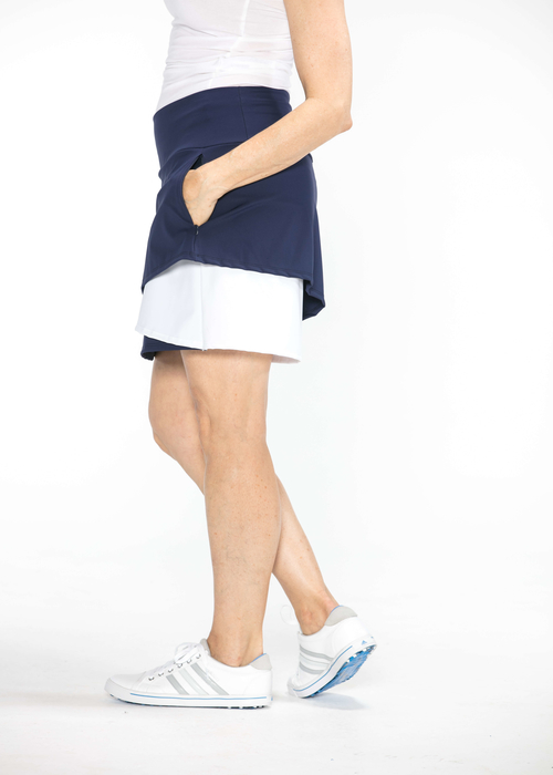 Side view of woman wearing a navy blue and white Wrap It Up golf skort