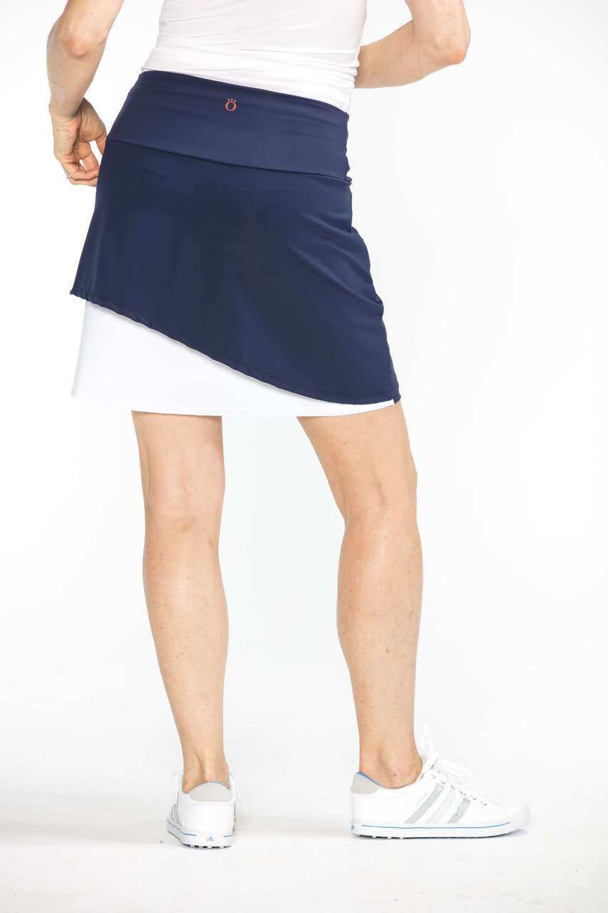 Woman with hands on her hips wearing a navy blue and white Wrap It Up golf skort