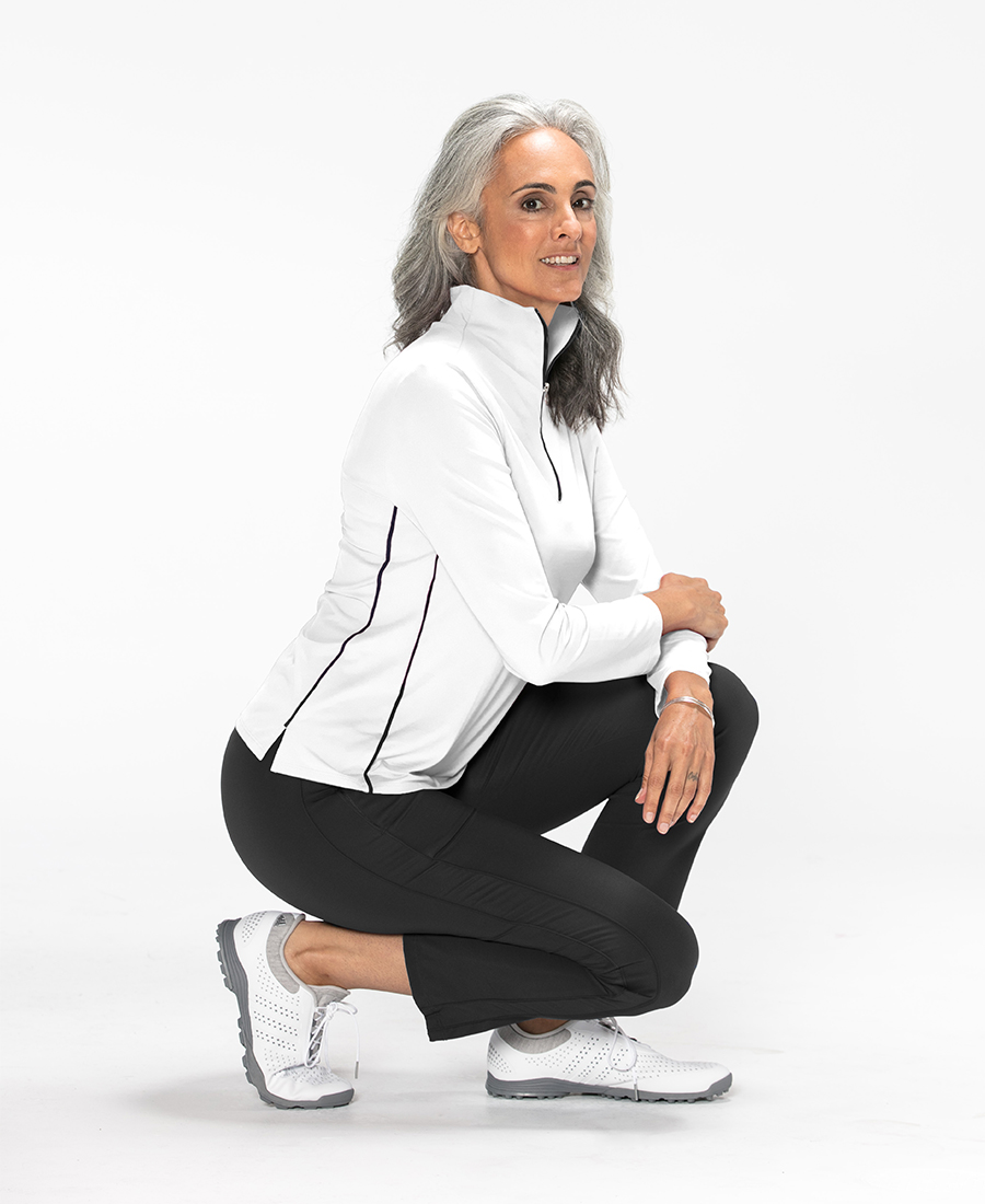 Side view of woman wearing a white longsleeve Keep it Covered golf top
