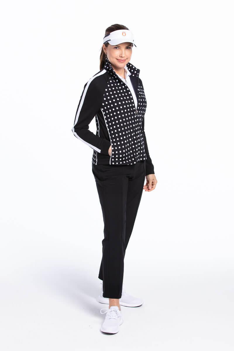 women golfer wearing black polka dot jacket, black pant and visor