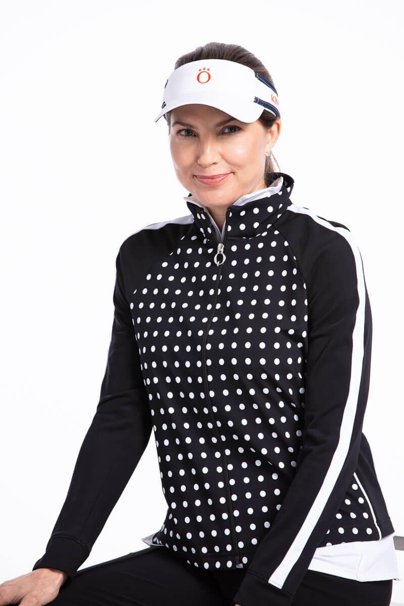 women golfer wearing black polka dot jacket and visor