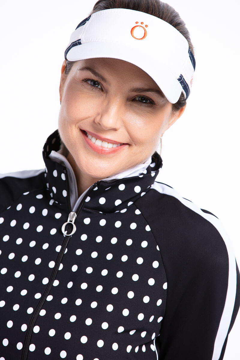 women smiling wearing a black polka dot golf jacket and visor