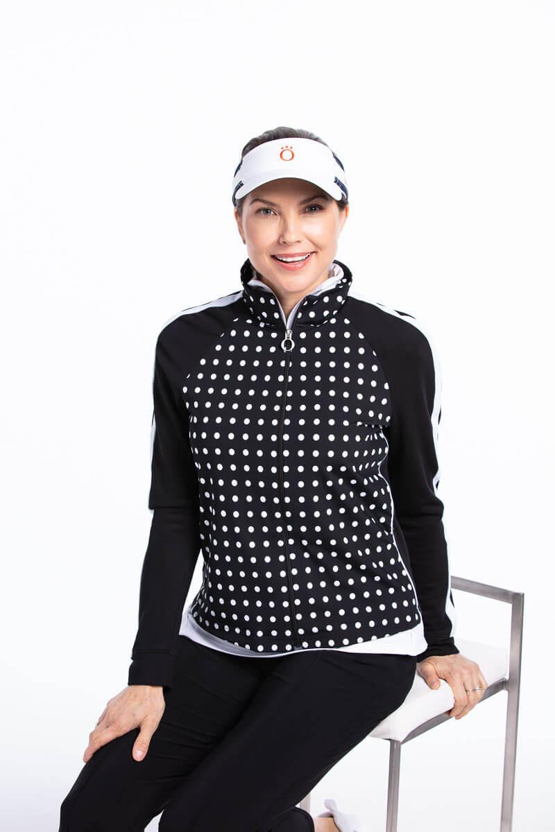women seated wearing a black polka dot golf jacket, black pant and visor.