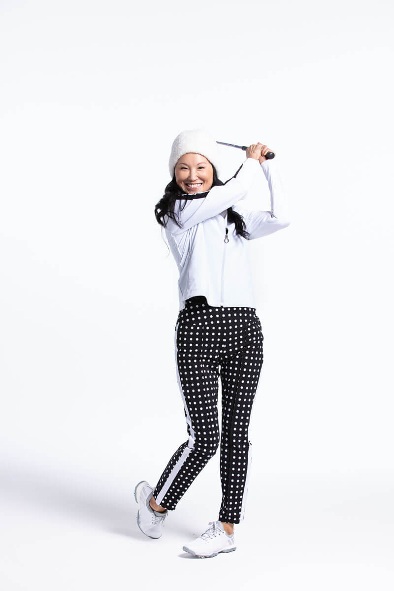 women  swinging a golf club wearing white lightweight golf jacket and polka dot pants