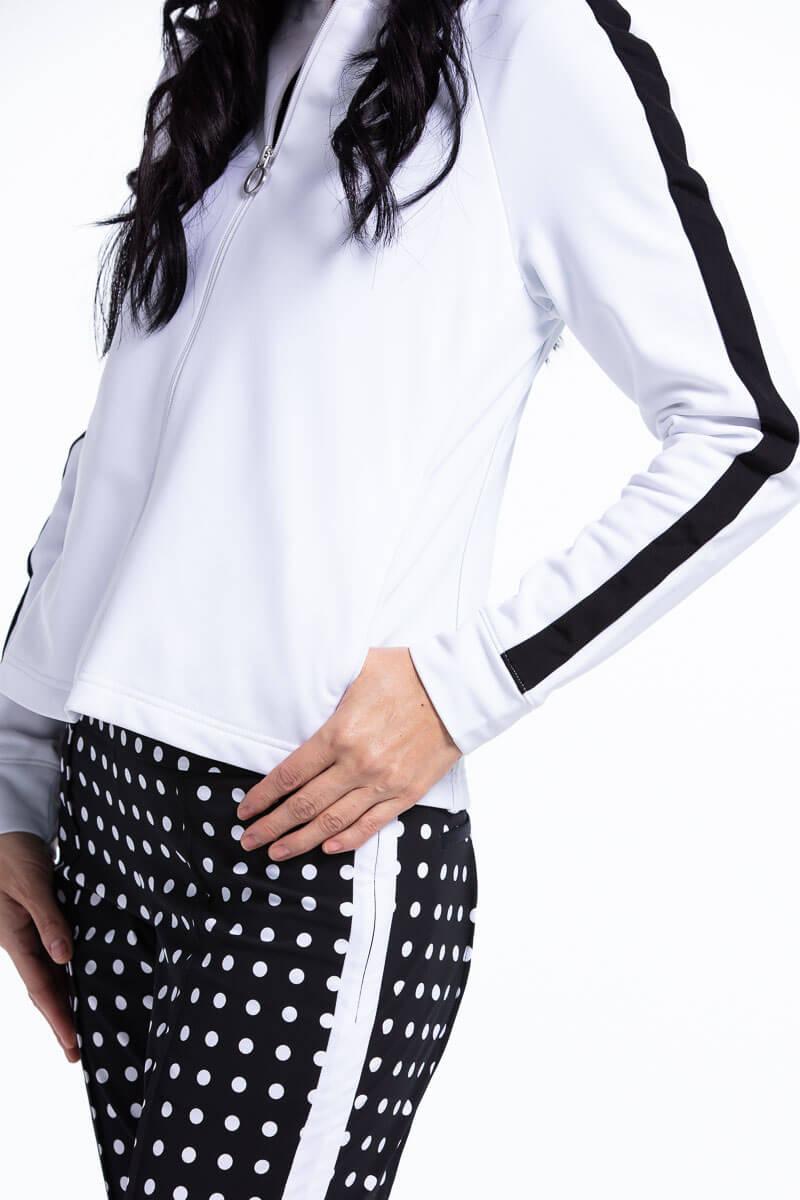 women wearing white lightweight golf jacket and black polka dot pants