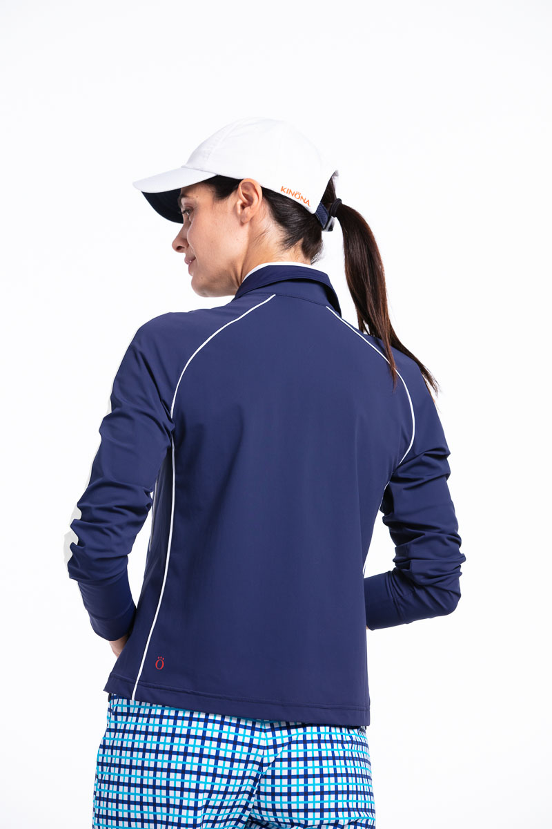 women golfer in navy blue jacket, blue check shorts and a golf cap.