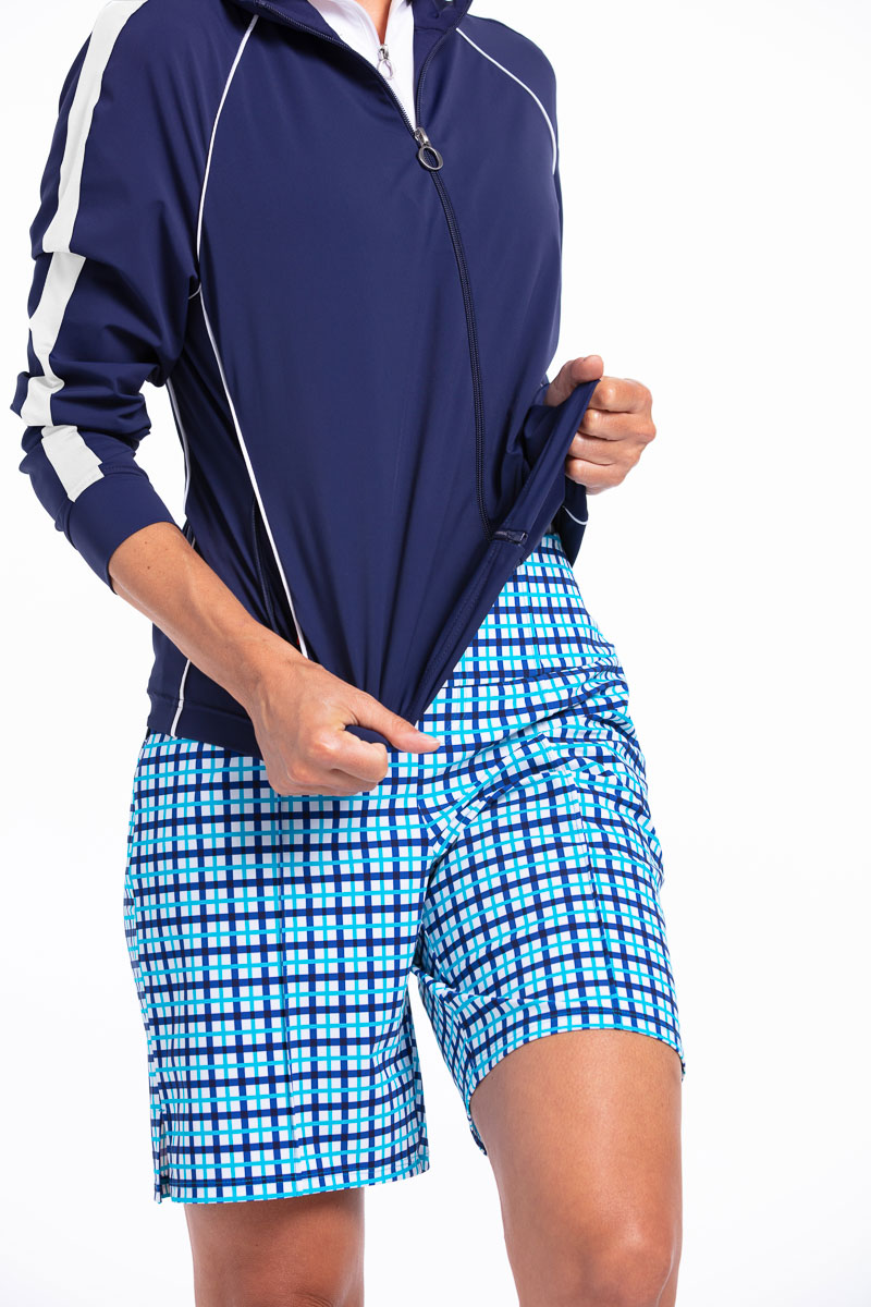 Woman golfer in navy blue Layer Up Jacket and Tailored and Tim golf shorts in Mediterranean check (blue).