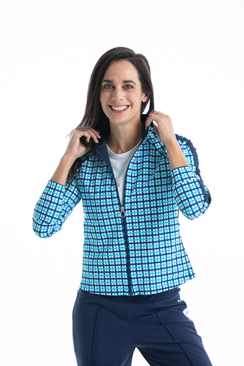 women golfer in blue check jacket and navy pants smiling.