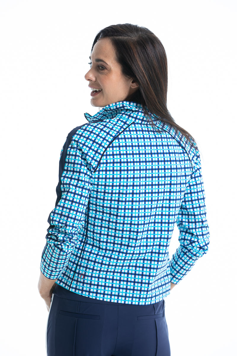 women in a blue check golf jacket with navy pants.