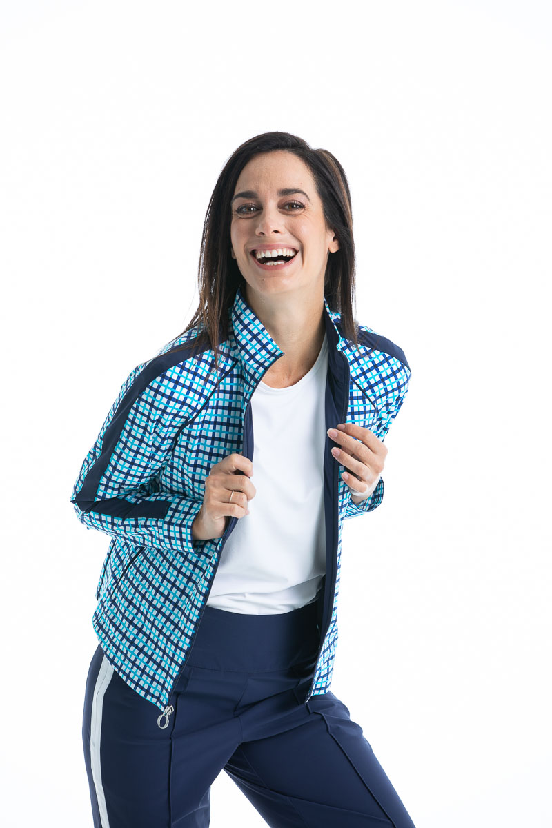 women golfer in a blue check jacket laughing.