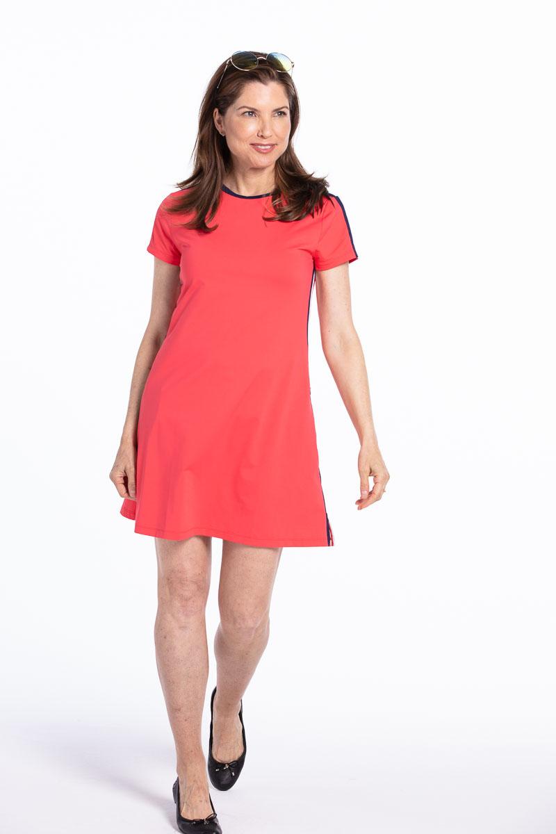 women golfer in a red tee shirt style golf dress walking.