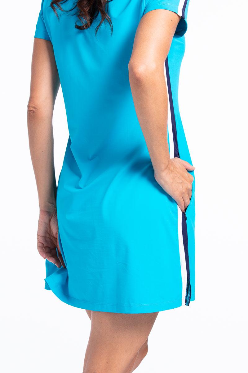 women golfer in a bright blue golf dress putting her hand in her pocket