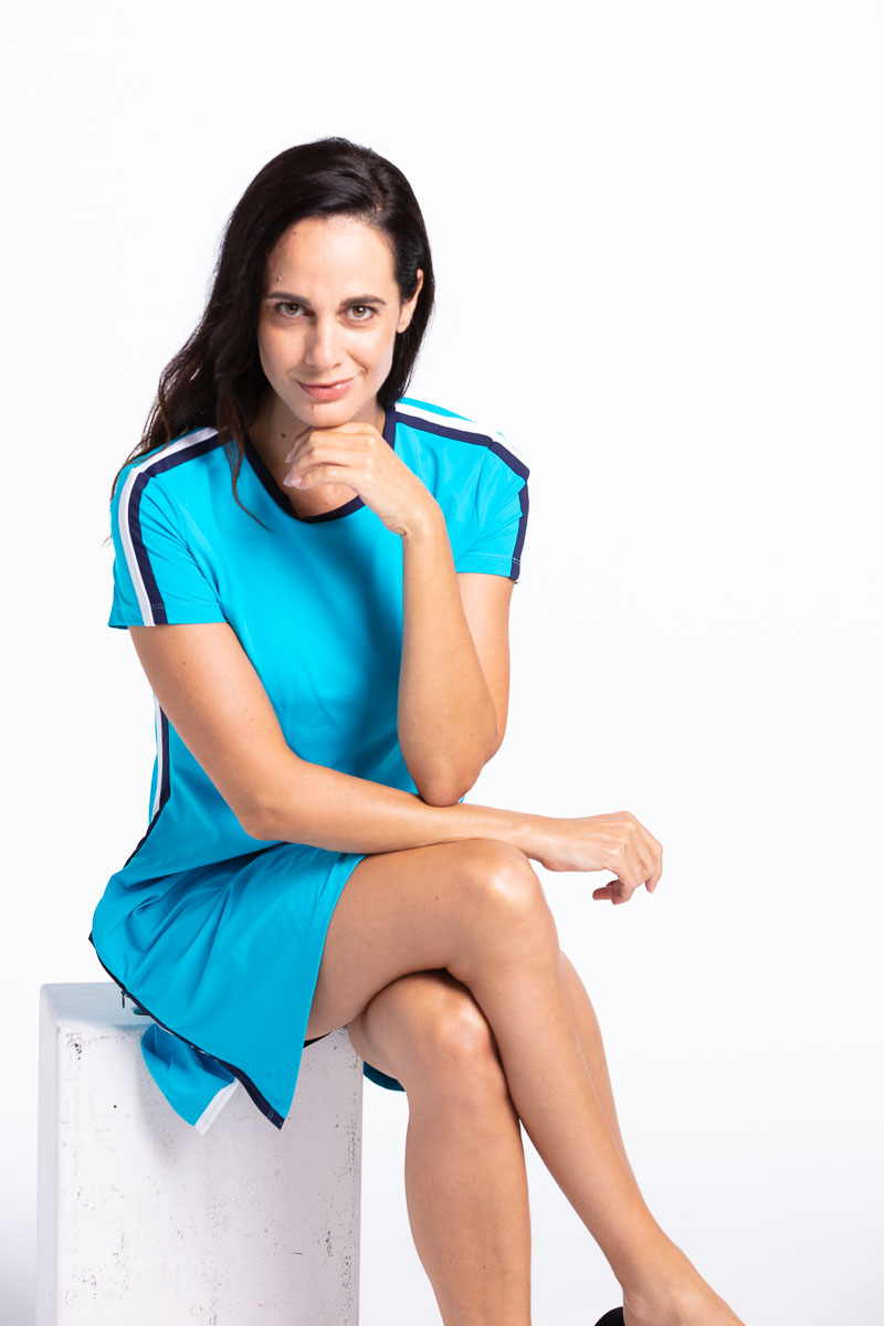 women golfer sitting and smiling in her bright blue golf dress.