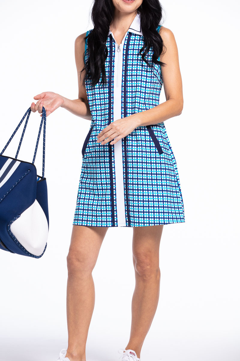 women golfer in a blue plaid golf dress holding a bag.