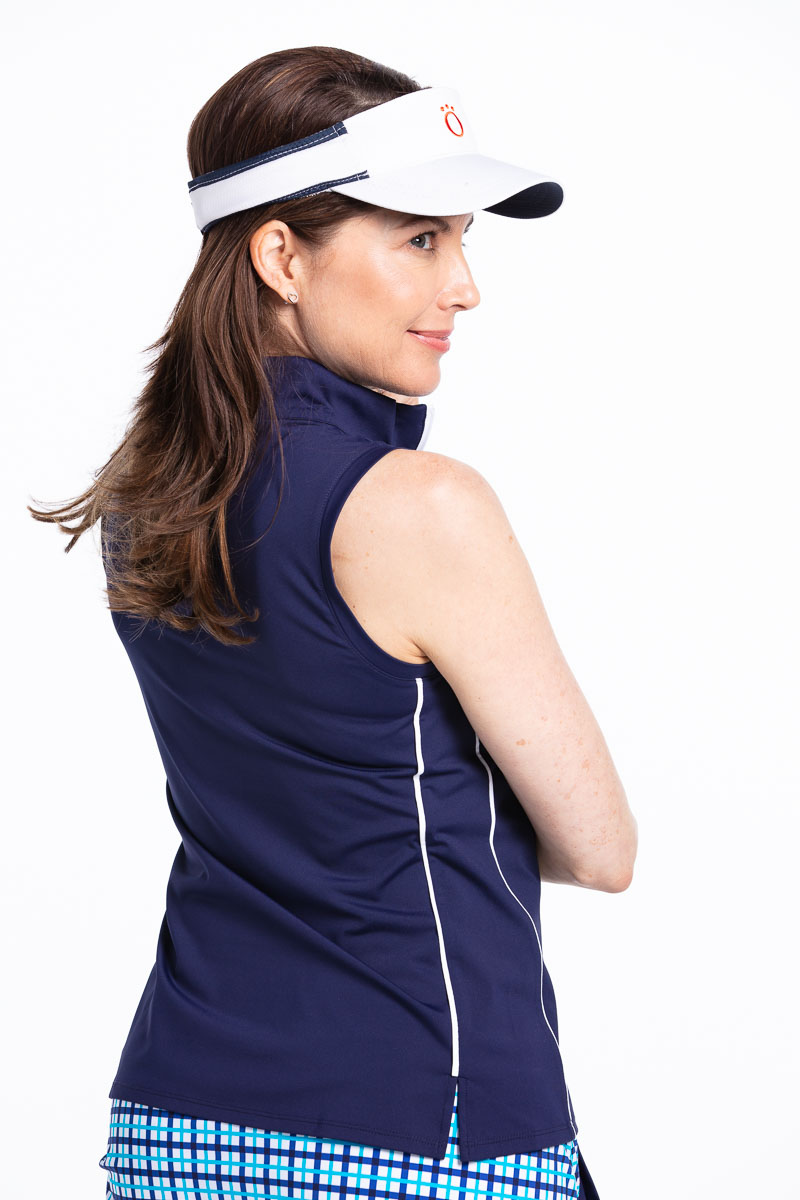 women golfer smiling in a navy sleeveless golf top and visor.