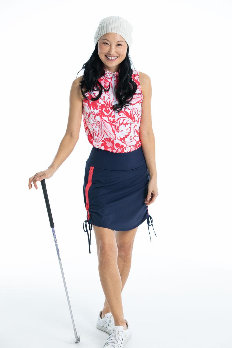 women golfer in pink floral sleeveless golf top and navy golf skort holding a golf club.