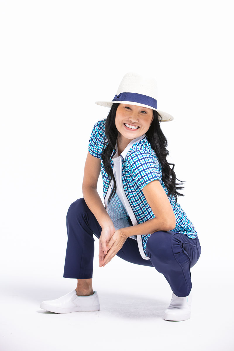 women smiling wearing a blue check shirt and navy pant with white fedora crouching.