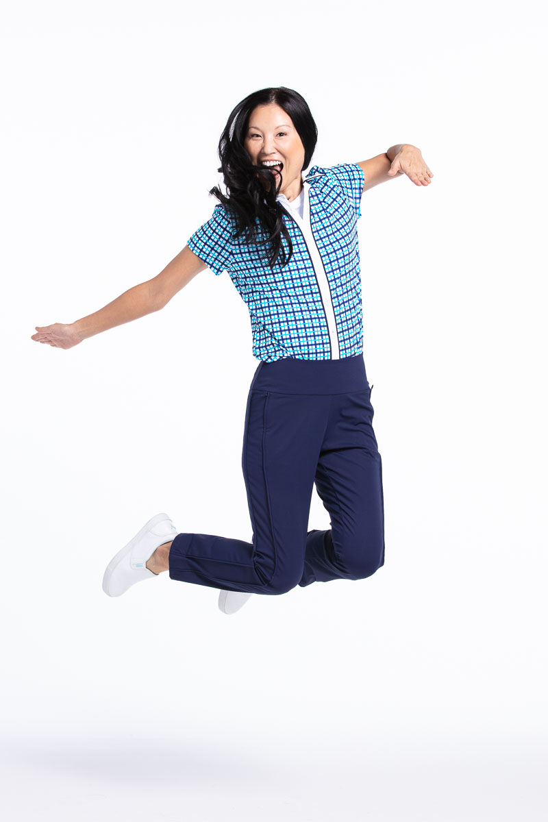 women jumping in the air wearing a blue check golf shirt and navy golf pants.