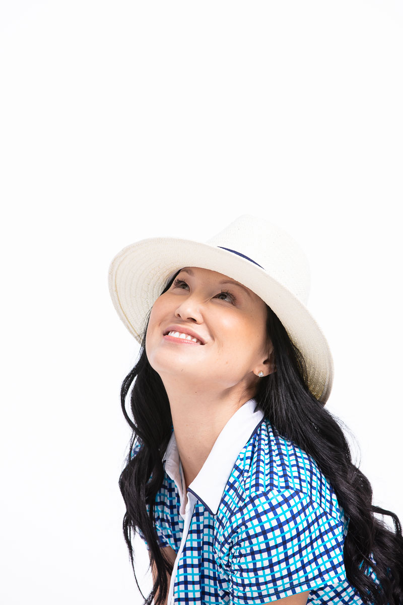women smiling and looking up at the sky wearing a blue check golf shirt and white fedora hat.