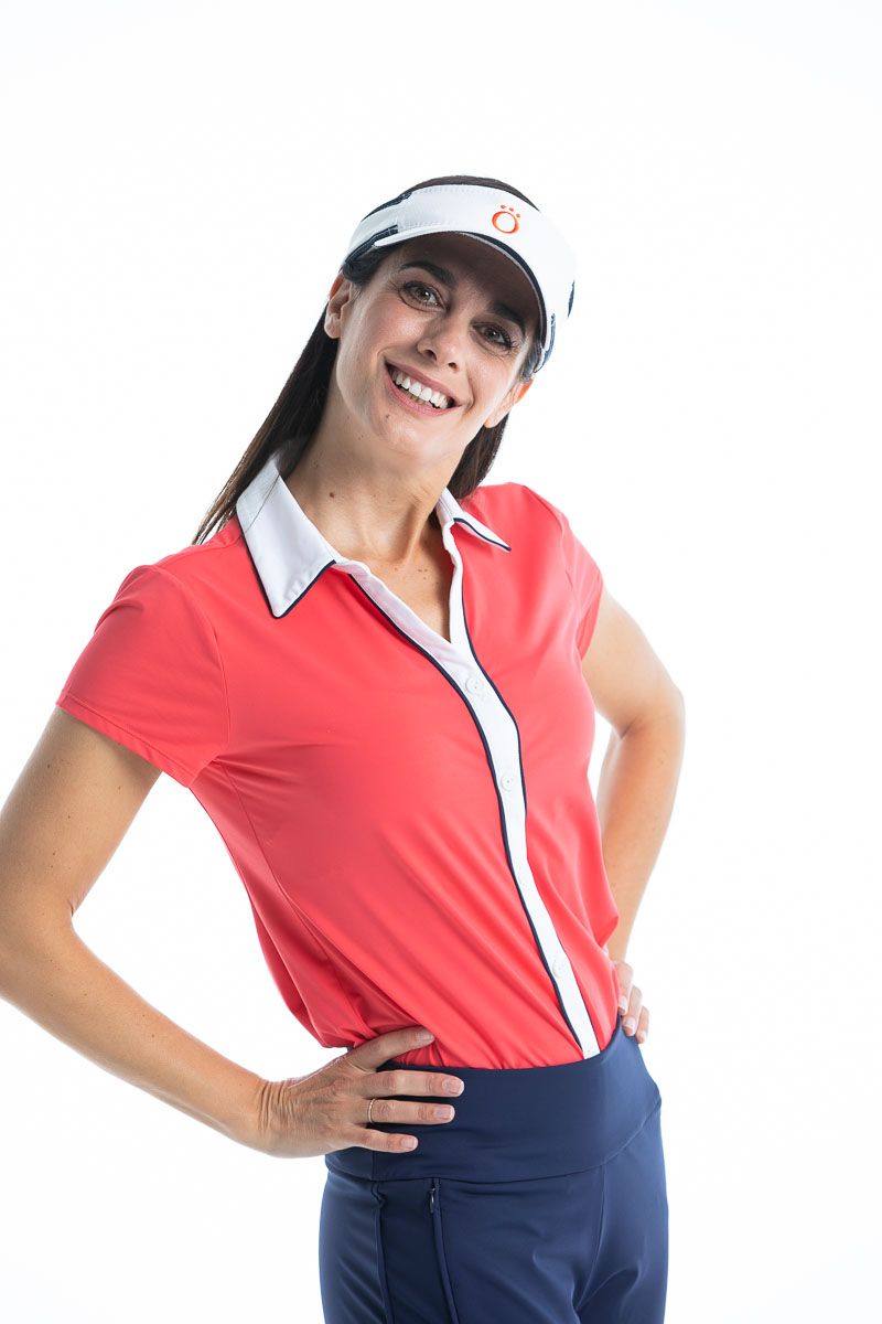 Woman golfer in watermelon red Class Act shortsleeve golf shirt and white No Hat Hair visor