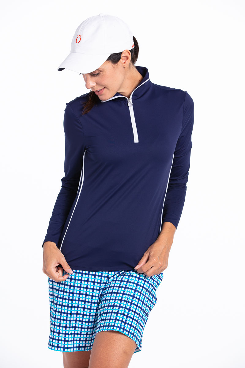 Woman golfer looking down wearing a navy blue Keep It Covered longsleeve golf top, blue check shorts, and a white We've Got You Covered golf hat.