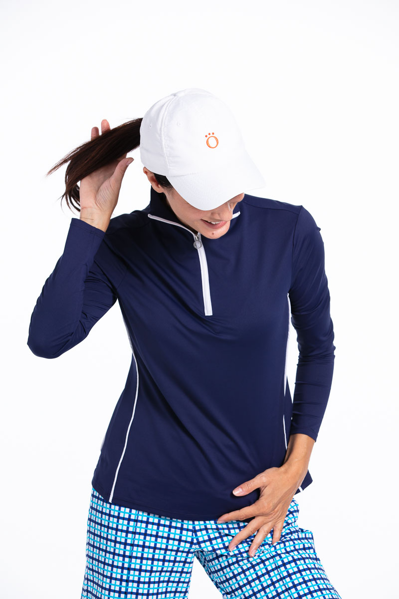 women golfer looking down and flipping her ponytail wearing a navy longsleeve golf shirt, blue check shorts and a white golf hat.