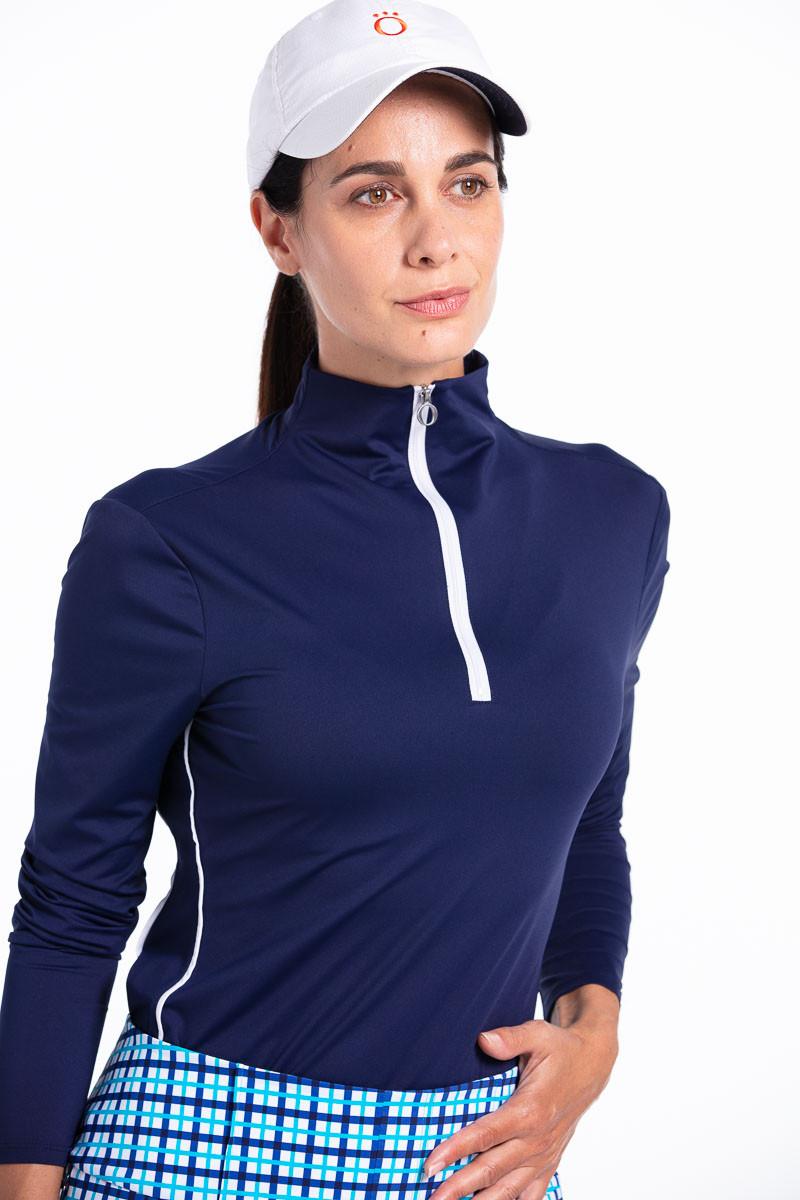 women golfer wearing a navy longsleeve golf shirt, blue check shorts and a white golf hat.