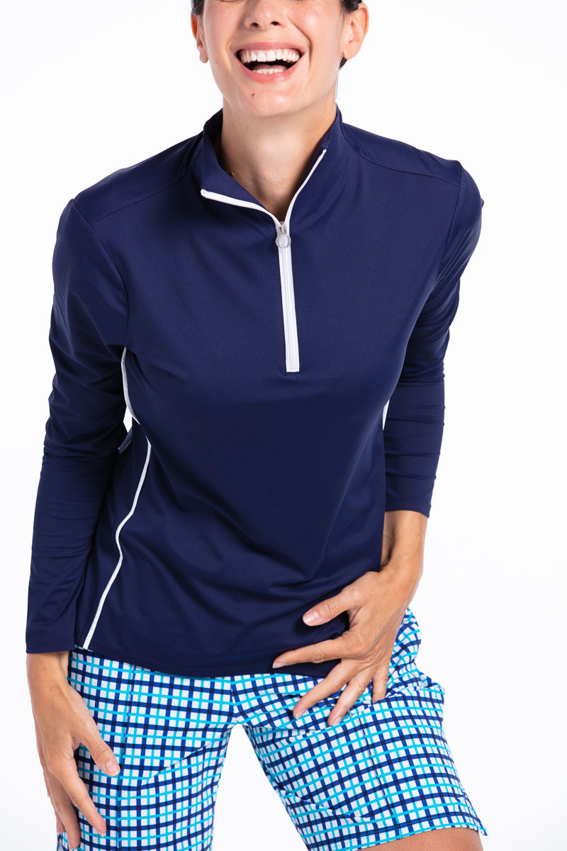 women golfer smiling wearing a navy longsleeve golf shirt, blue check shorts and a white golf hat.