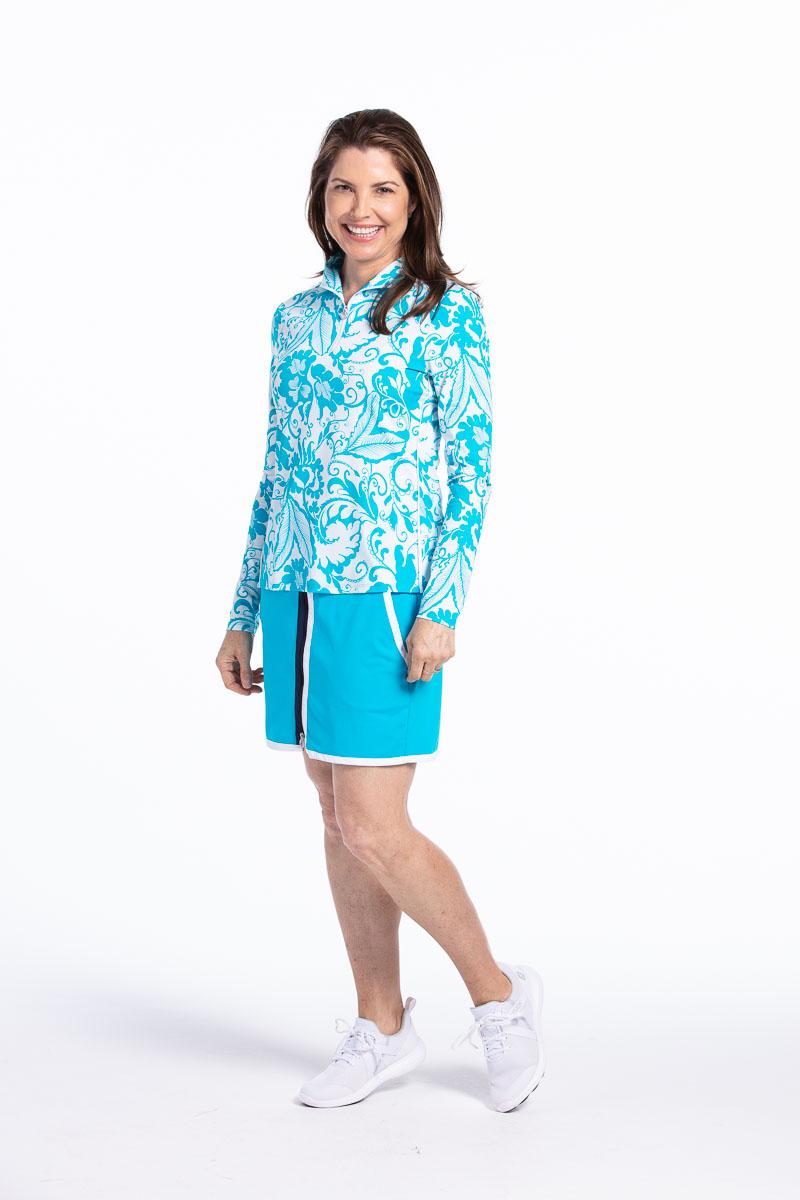women golfer wearing floral blue longsleeve golf top and matching blue golf skort.