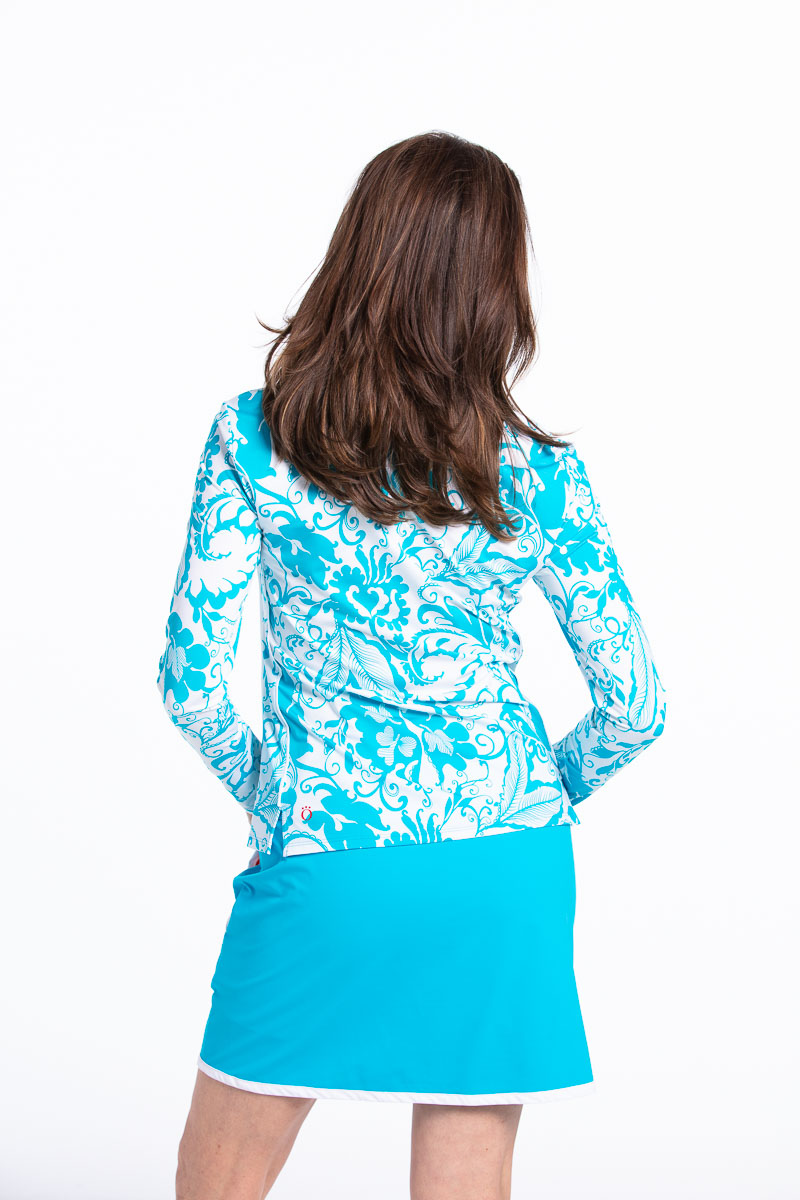 back view of women wearing a floral blue longsleeve golf top and matching blue golf skort.
