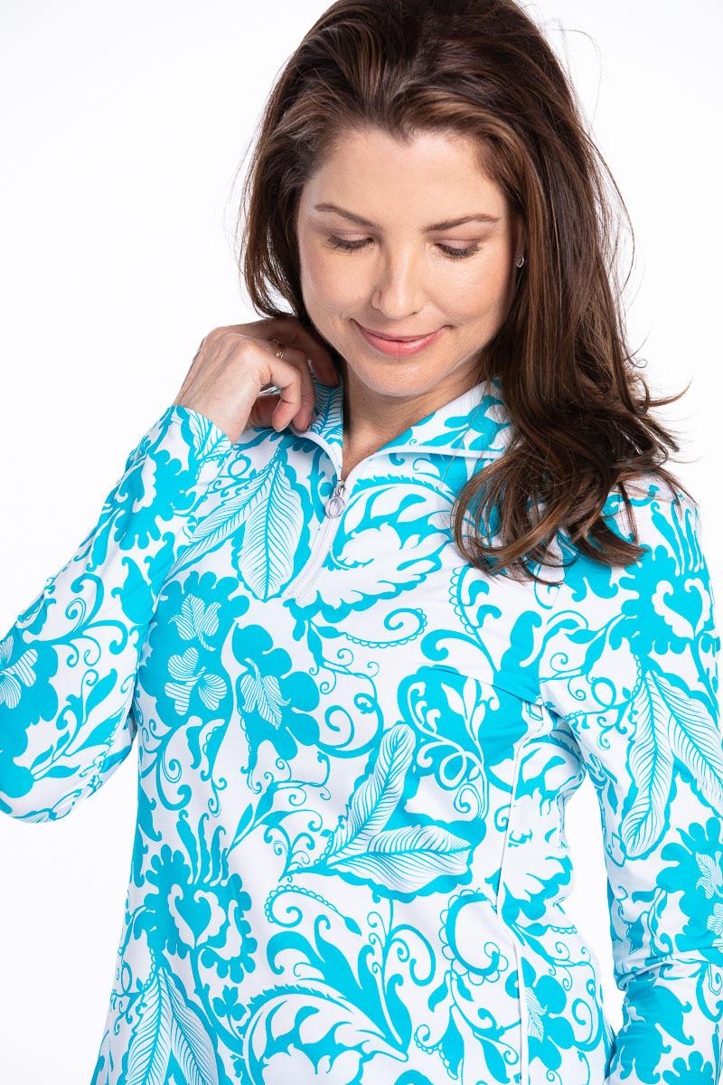 women looking down wearing a longsleeve floral blue golf shirt.
