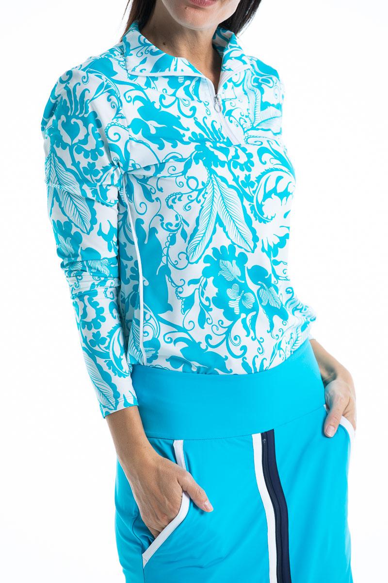 women wearing longsleeve floral blue golf top and matching blue skort.