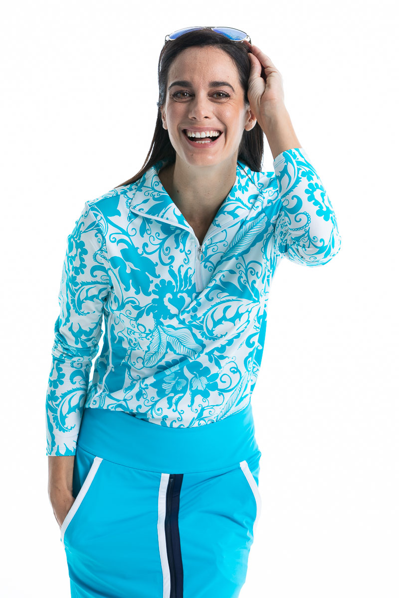 women smiling and putting sunglasses on top of her head wearing a floral blue and white longsleeve golf top and matching blue skort.