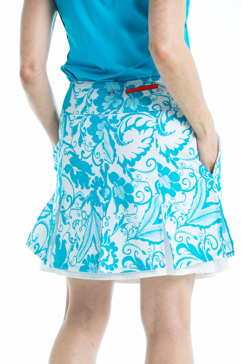 back view of a women wearing a bright blue floral print golf skort and matching solid blue golf top