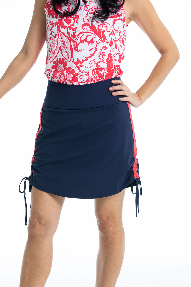 Woman golfer with hand on hip wearing a navy blue Rouched and Ready golf skort with red trim
