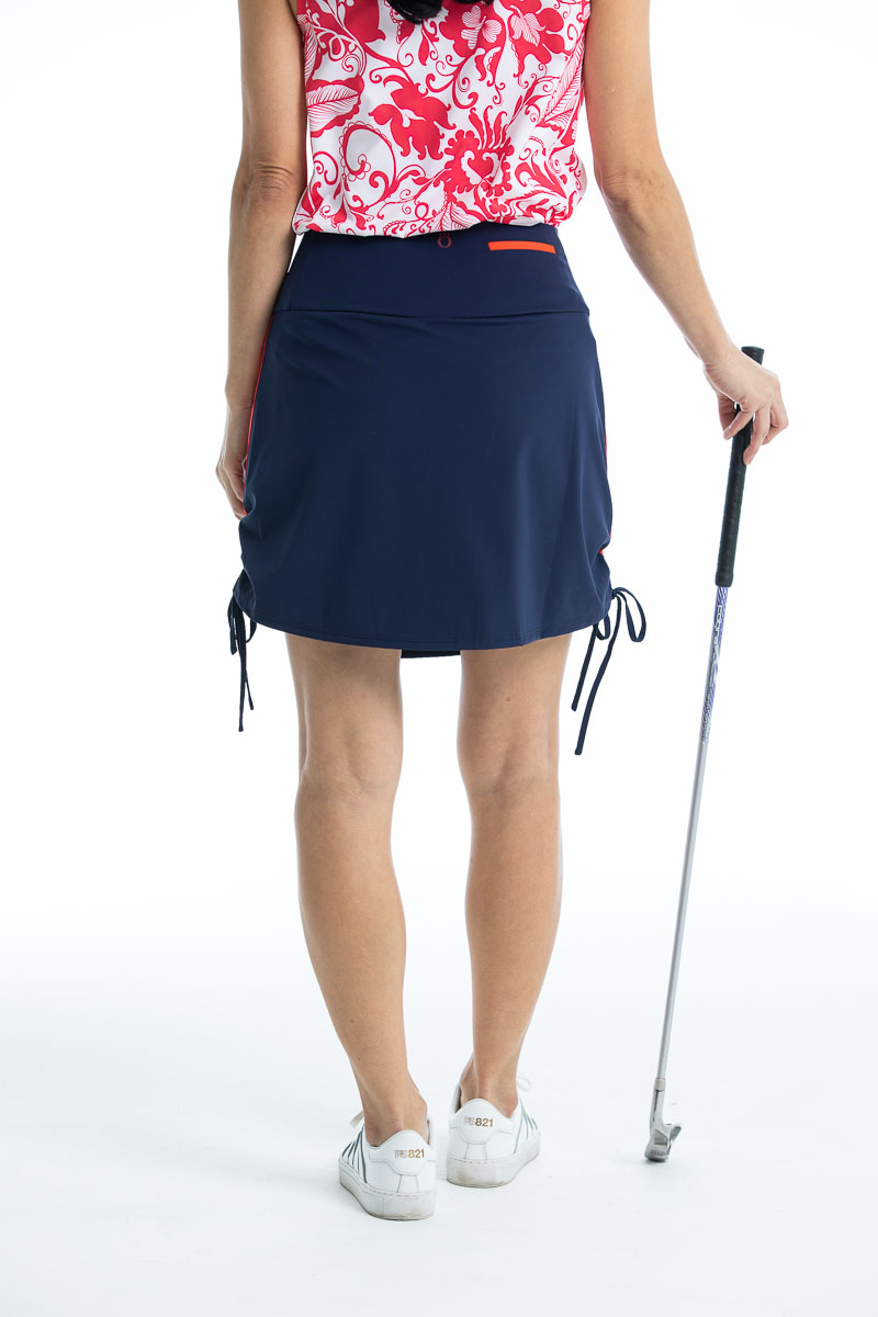 Woman holding a golf club wearing a navy blue Rouched and Ready golf skort