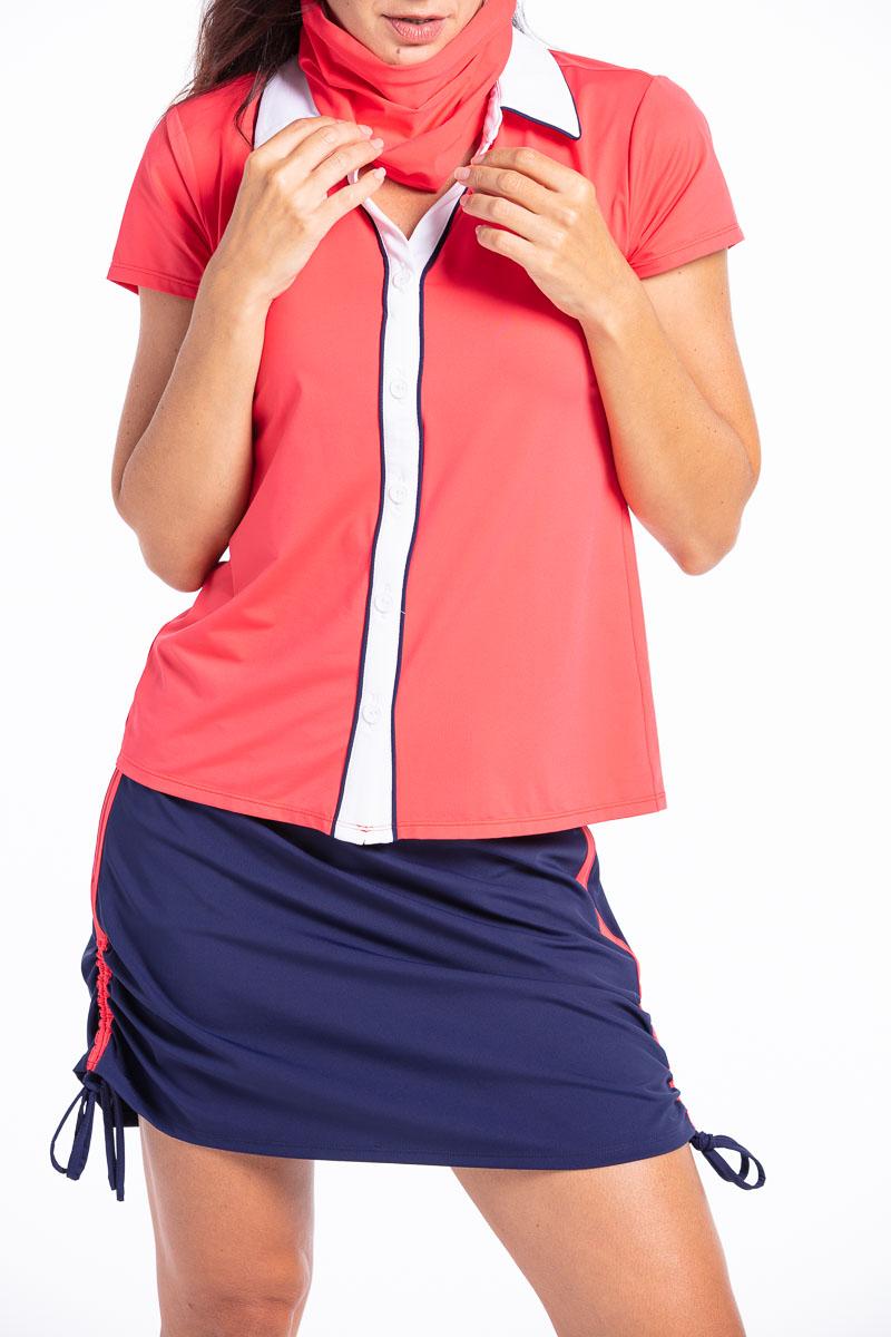 women wearing a red golf shirt with matching navy golf skort.