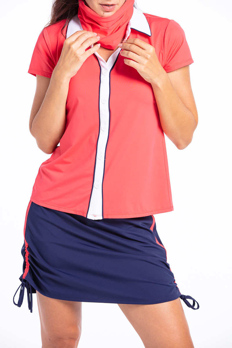 Woman wearing a watermelon red Class Act shortsleeve golf shirt with a navy blue Rouched and Ready golf skort.