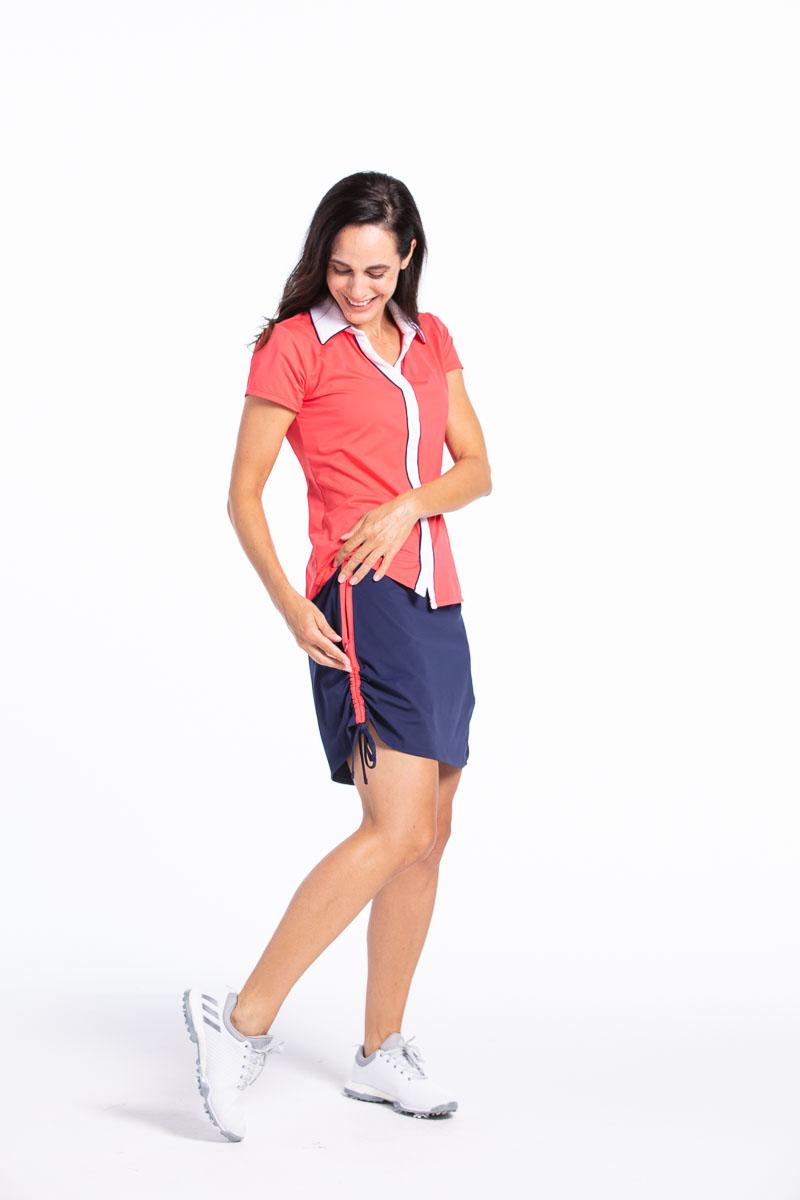 women golfer looking down to un zip the pockets on her navy blue golf skort.