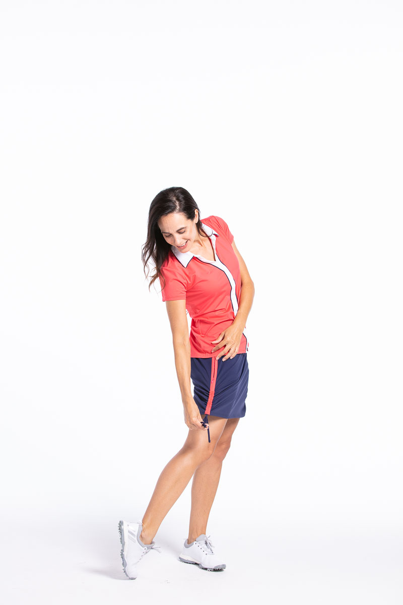 Woman looking down wearing a watermelon red Class Act shortsleeve golf shirt with a navy blue Rouched and Ready golf skort.