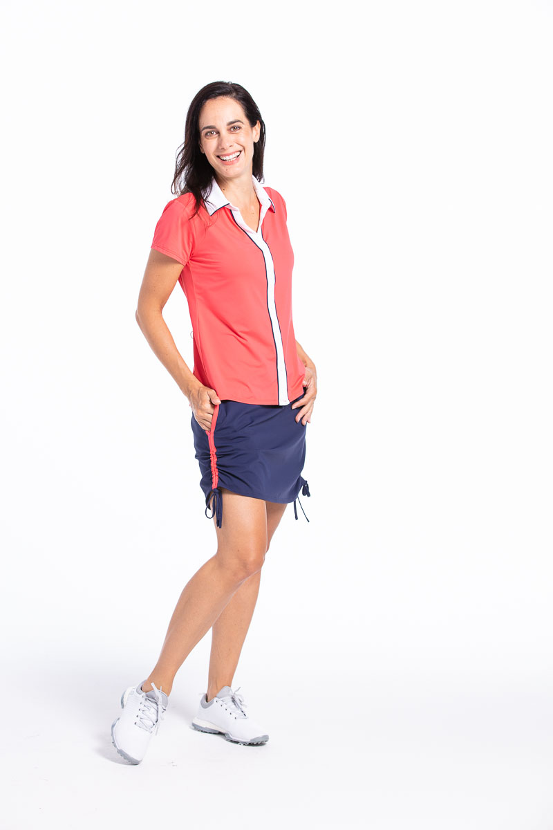 Woman golfer wearing a watermelon red Class Act shortsleeve top and a navy blue Rouched and Ready golf skort with her hands on her hips.