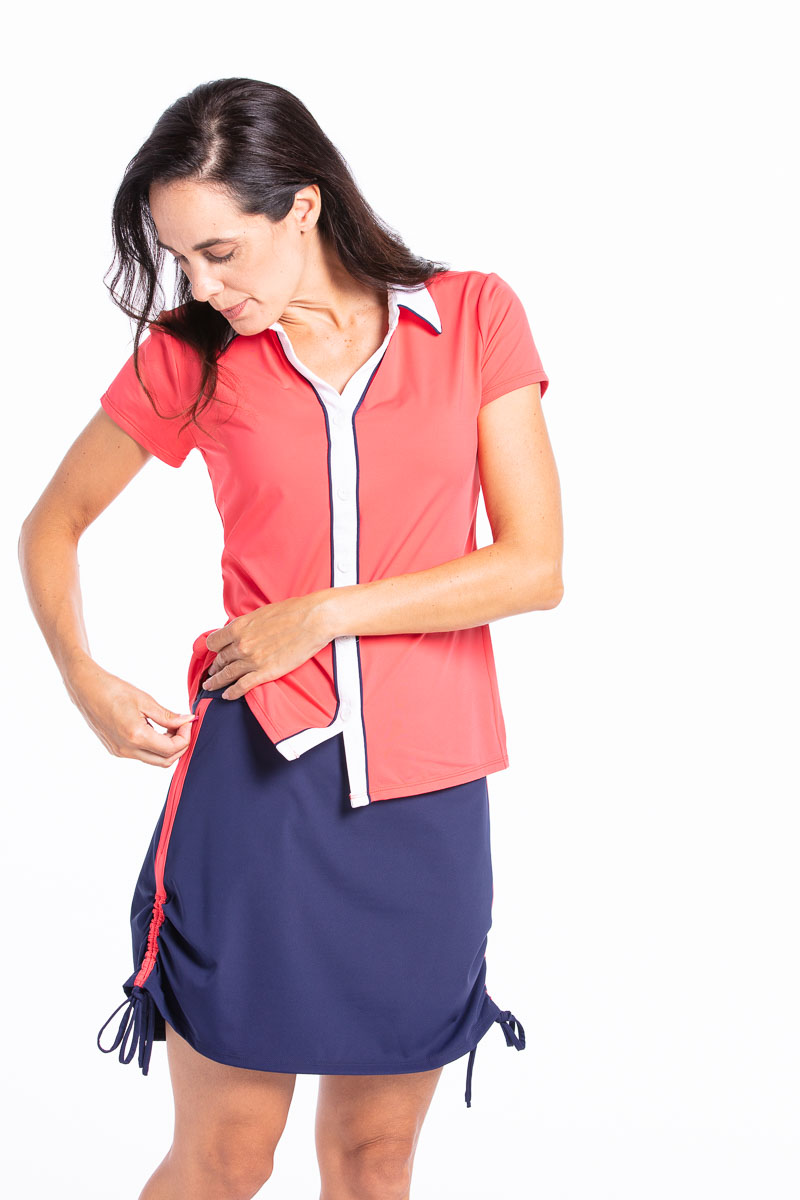 Woman looking down to unzip the pockets on her navy blue Rouched and Ready golf skort. Also wearing a watermelon red Class Act shortsleeve golf shirt.