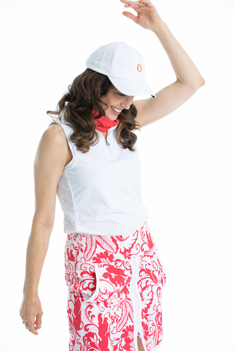 women with her left arm in the air looking down and wearing a white sleeveless golf top and matching pink floral golf skort.