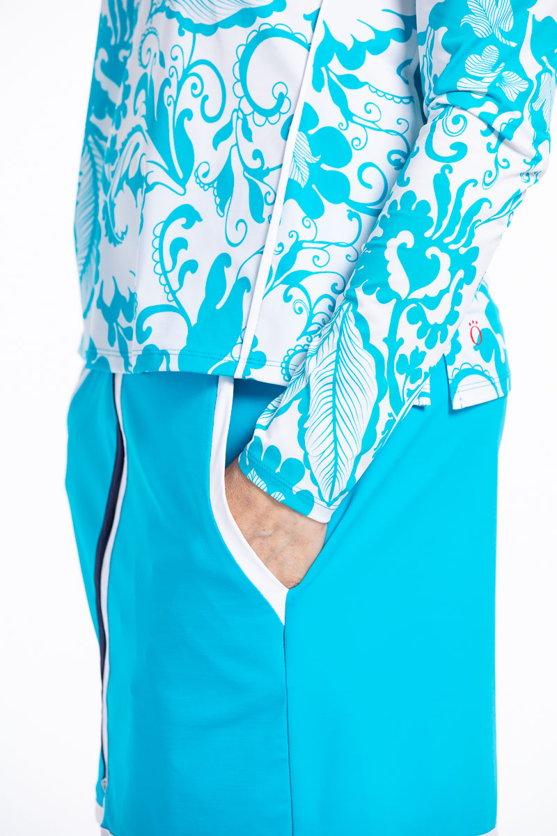 women side view with hand in her pocket wearing longsleeve floral blue golf top and matching solid blue golf skort.